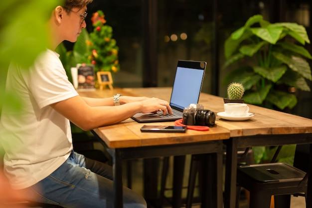 Freelancer masculino que trabalha no portátil em tardio na cafetaria. Foto Premium