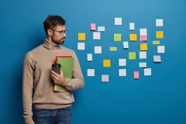 Freelancer ou estudante masculino lê ideias escritas em notas de papel coladas na parede azul, segura café para viagem e um bloco de notas, aprende palavras estrangeiras com adesivos coloridos Foto gratuita