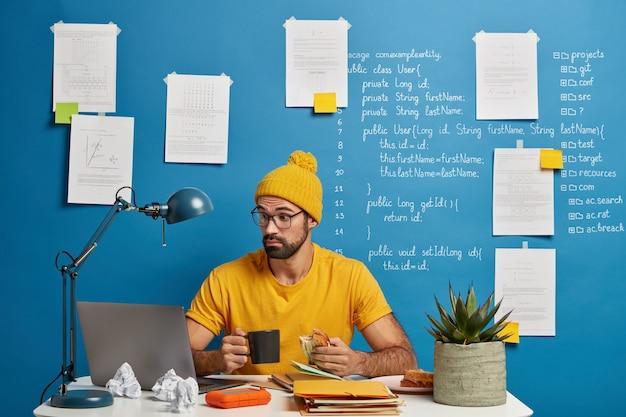 Freelancer profissional masculino de ti surpreso focado em monitor de laptop, tenta melhorar o código de aplicação, toma café e come sanduíche. Foto gratuita