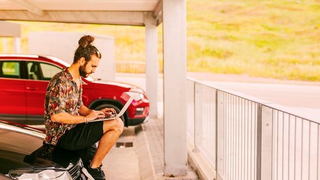Freelancer sentado no capô e trabalhando remotamente Foto gratuita