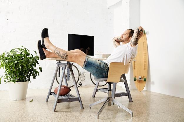 Freelancer tatuado e relaxante, sonhadoramente olhando pela janela, enquanto faz uma pausa no trabalho, com as pernas na mesa dentro de um grande loft branco Foto gratuita
