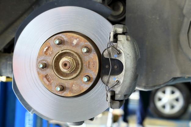 Freios a disco em carros em processo de substituição de pneus novos na garagem. Foto Premium