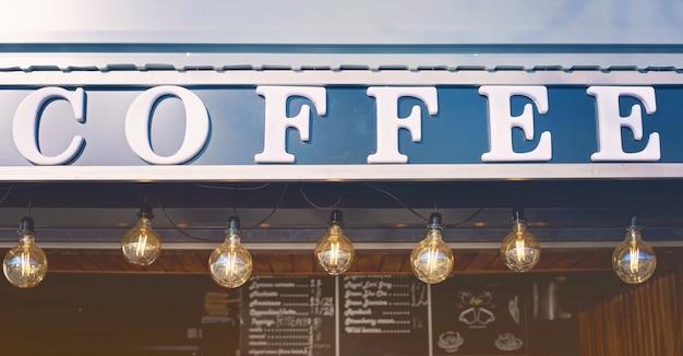 Frente de loja de café com luzes de bulbo e quadro-negro Foto Premium