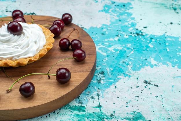 Frente fechar bolo cremoso com cerejas frescas isoladas em mesa azul claro, bolo de cor de bolo de biscoito creme Foto gratuita