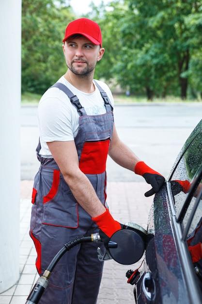 Frentista do posto de gasolina com um bico de combustível nas mãos, enchendo o tanque do carro do cliente Foto Premium