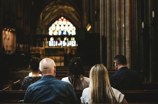 Frequentadores da igreja sentado no banco da igreja Foto Premium