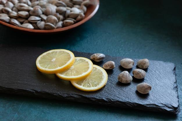 Fresco cru surf clam chamelea gallina com limão sobre a tábua de corte de pedra Foto Premium