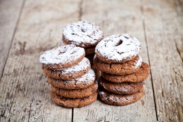 Fresh cozido biscoitos de chocolate com pilhas de pó de açúcar na mesa de madeira Foto Premium