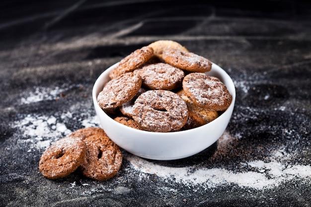 Fresh cozido biscoitos de chocolate e biscoitos de aveia com monte de açúcar em pó em tigela branca Foto Premium