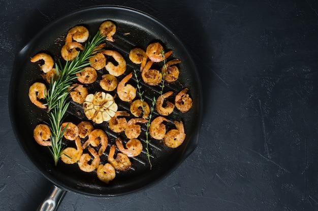 Frigideira com gambas fritas e raminhos de alecrim e tomilho. Foto Premium