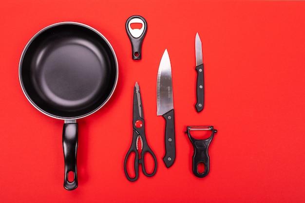 Frigideira com utensílios de cozinha, isolado em fundo vermelho Foto Premium