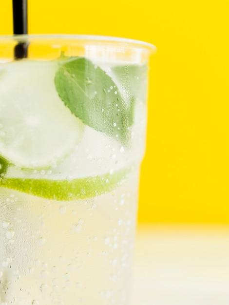 Frio branco saboroso cocktail com limão, hortelã e gelo em fundo amarelo Foto gratuita