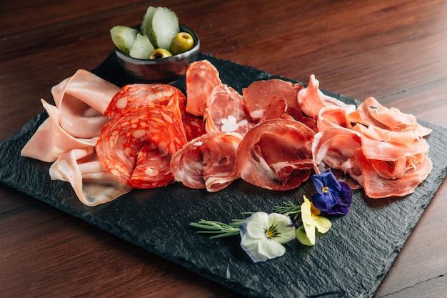Frios na placa de pedra com presunto, bacon, salame e salsichas. Foto Premium
