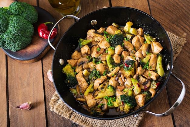 Frite frango com brócolis e cogumelos - comida chinesa Foto Premium
