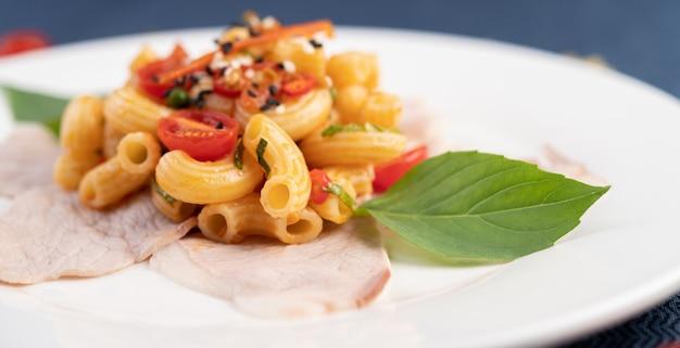 Frite o macarrão na carne de porco superior aproximadamente em um prato branco. Foto gratuita
