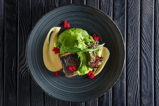 Frito pedaço de salmão com molho cremoso e salada verde folhas decoradas com caviar Foto Premium