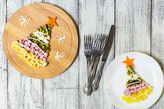Fromsalad da árvore de natal mais olivier no prato sobre uma mesa de madeira branca. vista do topo Foto Premium