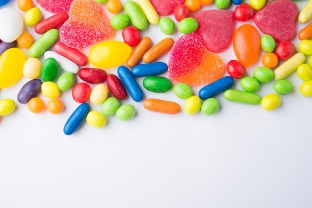 Fronteira de balas de gelatina colorida em branco Foto Premium