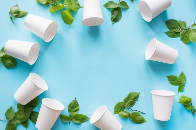 Fronteira de copo descartável branco e folhas verdes em azul Foto Premium