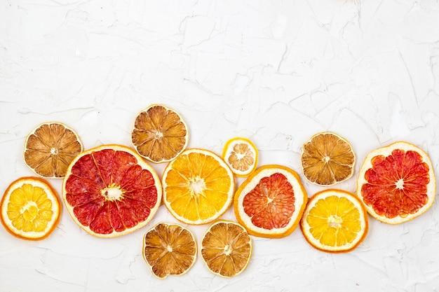 Fronteira de fatias secas de várias frutas cítricas em fundo branco. copos de laranja limão toranja Foto Premium