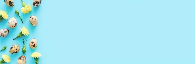 Fronteira de flores e ovos de primavera. flores amarelas e ovos de codorna em fundo azul com espaço de cópia. banner de vista superior criativo flat lay. Foto Premium