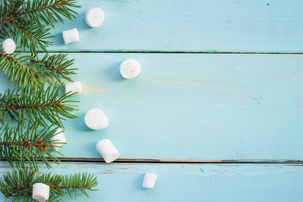 Fronteira de natal com galho de árvore do abeto e marshmallows em fundo de madeira Foto Premium