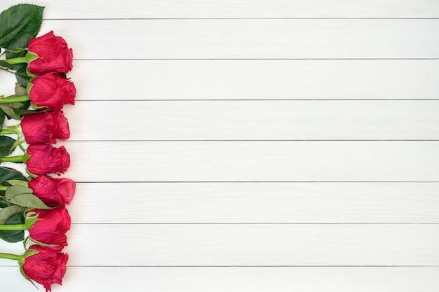 Fronteira de rosas vermelhas em fundo branco de madeira. vista de cima, copie o espaço Foto Premium