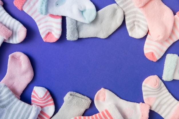 Fronteira feita com muitas meias do bebê em fundo azul Foto gratuita