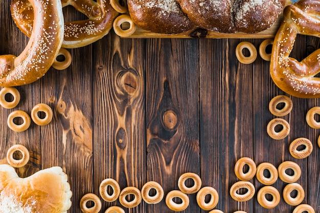 Fronteira feita com pão trançado recém-assados, pretzels e bagels no fundo de madeira Foto gratuita