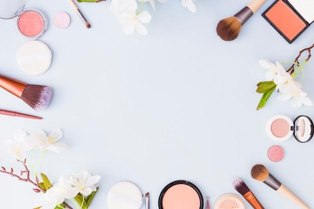 Fronteira feita com produtos cosméticos e flores sobre fundo azul Foto gratuita