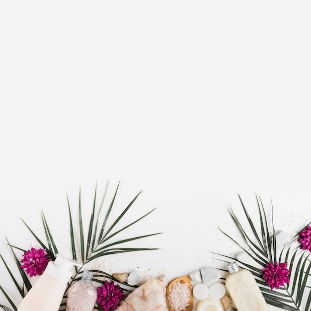 Fronteira inferior com flor; sai; pedras de spa; esfoliação corporal e sal no fundo branco Foto gratuita