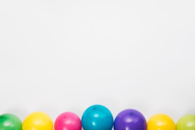 Fronteira inferior feita com balões coloridos no fundo branco Foto gratuita