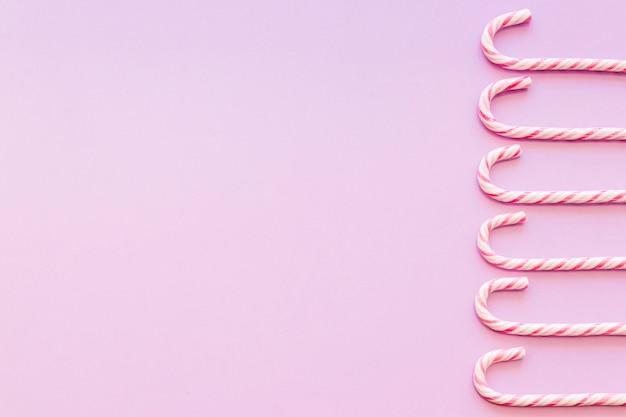 Fronteira lateral feita com doces de bengala de natal em fundo rosa Foto gratuita