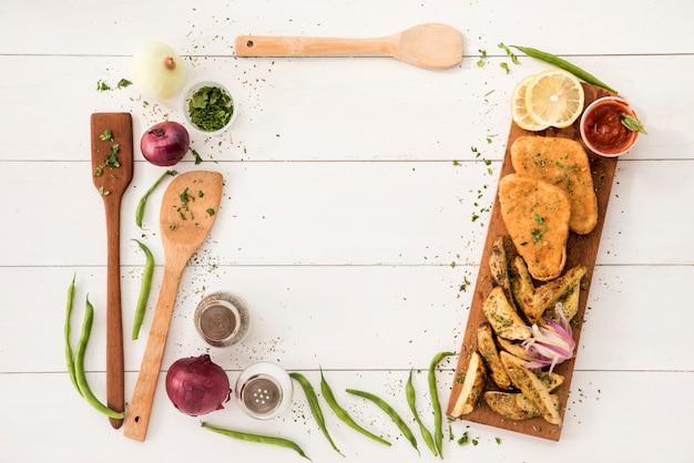 Fronteira organizando de utensílios de cozinha e refeição pronta na mesa de madeira Foto gratuita