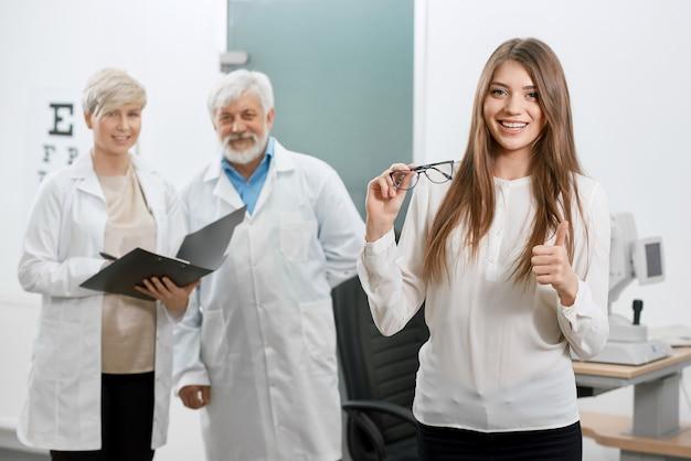 Frontview do paciente satisfeito que sorri na frente do oculista idoso e do assistente. Foto Premium