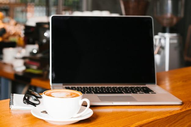 Frontview laptop e café na superfície de madeira Foto gratuita
