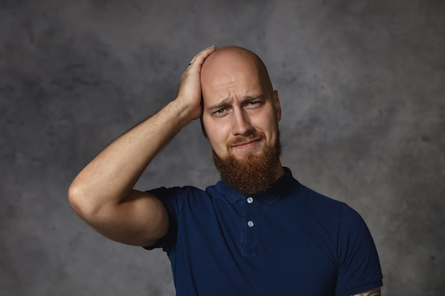 Frustrado, arrependido, jovem elegante com barba espessa, com expressão esquecida e perplexa, tocando sua cabeça raspada, tentando se lembrar de algo. um cara barbudo com uma terrível dor de cabeça Foto gratuita