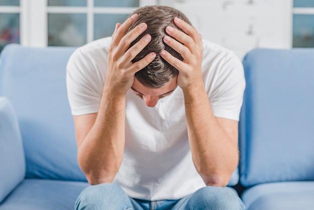 Frustrado, homem, sofrimento, de, dor de cabeça, sentar sofá Foto gratuita