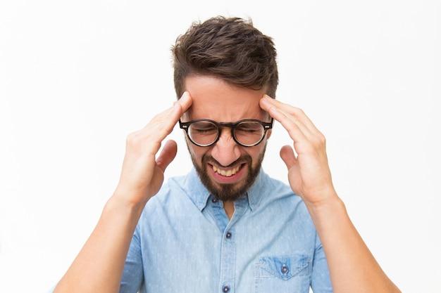 Frustrado infeliz cara tocando a cabeça com uma careta de dor Foto gratuita