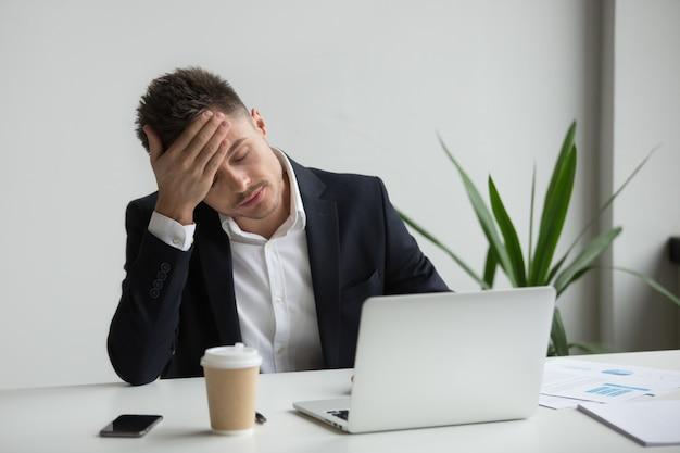 Frustrado, milenar, homem negócios, tendo, forte, dor de cabeça, cansado, de, laptop, trabalho Foto gratuita