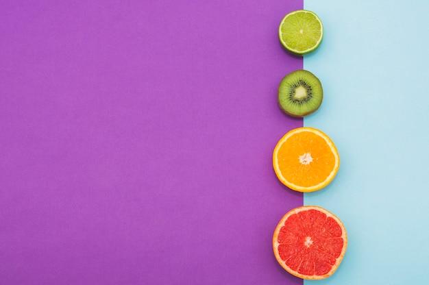 Fruta cítrica cortada ao meio; kiwi na fronteira de fundo duplo Foto gratuita