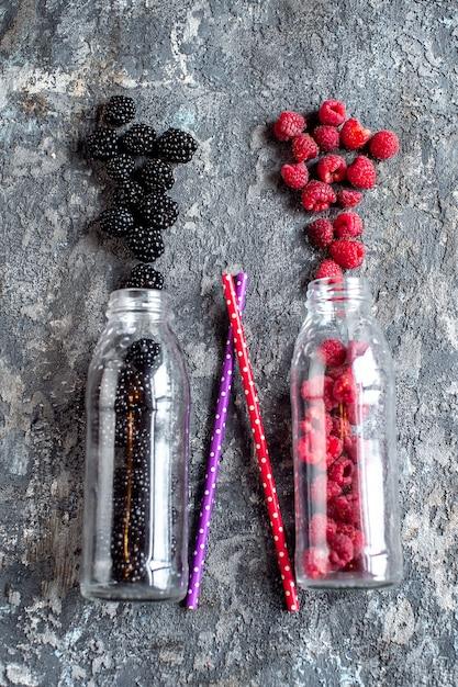 Fruta de amora e framboesa em garrafas de vidro com canudos Foto Premium