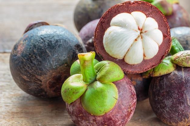 Fruta de mangostão no chão. descascados por carne branca no interior. Foto Premium