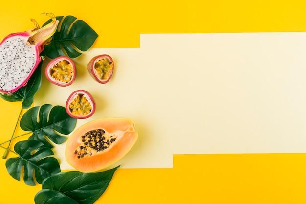 Fruta do dragão cortada ao meio; maracujá e mamão com folhas verdes artificiais sobre fundo amarelo Foto gratuita