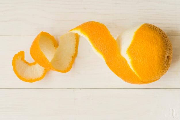 Fruta laranja descascada em fundo de madeira Foto gratuita