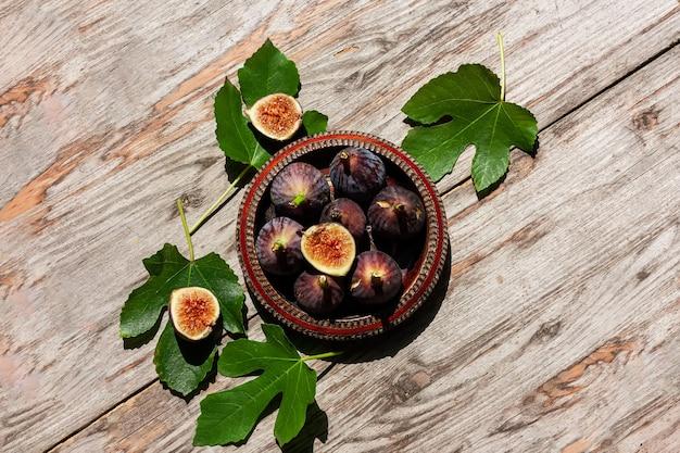 Fruta madura de figo roxo com folhas em uma tigela de madeira com fundo de madeira Foto Premium