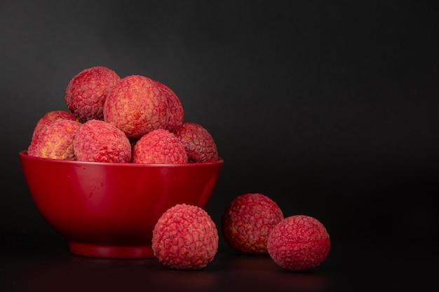Fruta vermelha do lichi colocada em uma cesta. Foto gratuita
