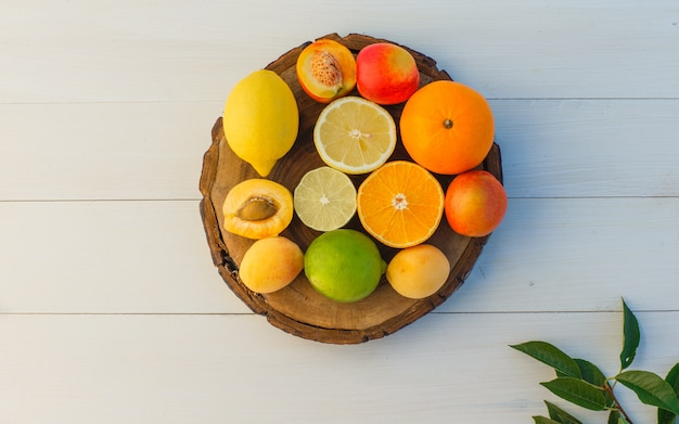 Frutas cítricas com folhas, damascos, nectarinas na tábua e fundo de madeira, postura plana. Foto gratuita
