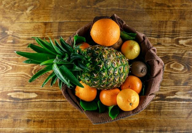 Frutas cítricas com kiwi, abacaxi, folhas de madeira e toalha de cozinha, vista superior. Foto gratuita