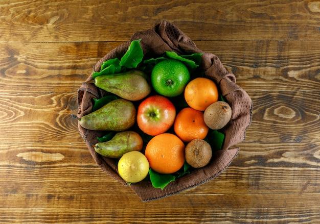 Frutas cítricas com maçãs, pêra, kiwi, folhas na mesa de madeira, vista superior. Foto gratuita